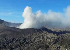 Smoking volcano Bromo and its landscape